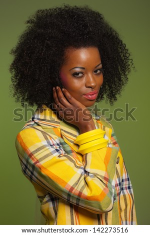 Afro woman in vintage seventies fashion style. Yellow jacket and green background.