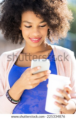 Afro woman with mobile phone and coffee  - stock photo