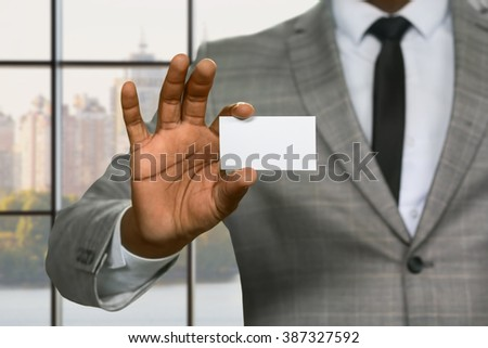Afroamerican employee shows visit card. Afro salesman with visit card. He's been invited to headquarters. Insurance agent in the city. - stock photo