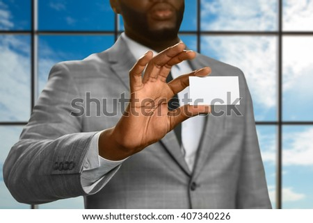 Afroamerican male shows visit card. Businessman on cloudy sky background. Company has a new boss. Time to introduce yourself. - stock photo