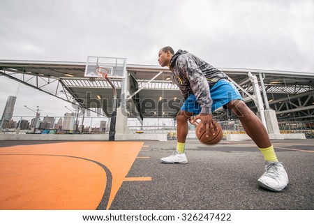 Afroamerican player playing basketball outdoors - Sportive man training in a basketball court - stock photo