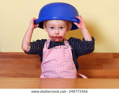 after licking the mixing bowl girl is holding the mixing bowl on her head; she has a cute chocolate mouth - stock photo