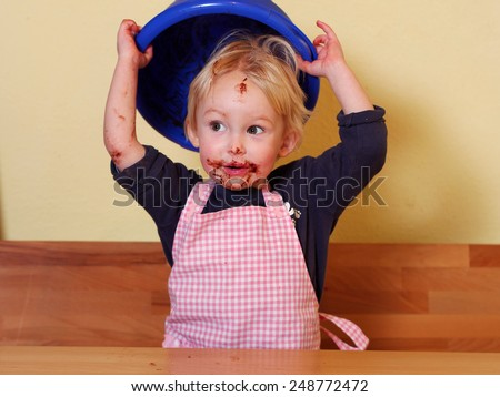 after licking the mixing bowl girl is holding the mixing bowl over her head; she has a funny chocolate mouth - stock photo