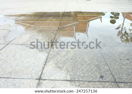 After rain in Bangkok - reflection of the temple in puddle - stock photo