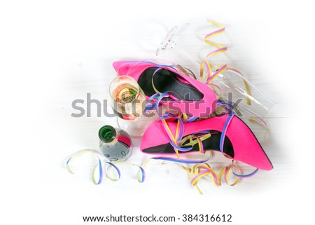 after the party, ladies pink high heels shoes lying on the floor, streamers, champagne glasses and bottle from a happy women's, valentines or mothers day, view from above, background fades to white - stock photo