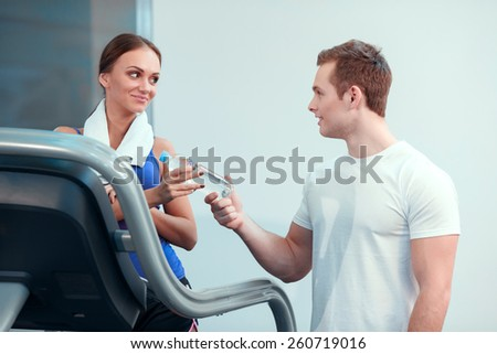 After the workout. Attractive young woman in sports clothing receiving a bottle of water from her instructor while standing on the treadmill in health club - stock photo