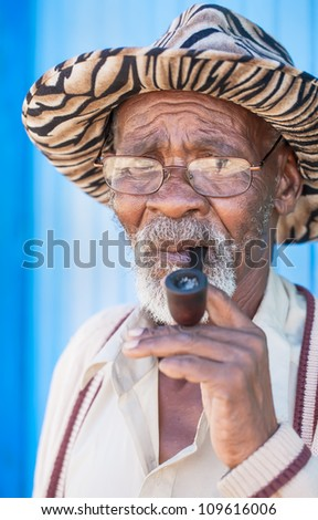 After tuff years, smoking his pipe is the highlight of the day. - stock photo