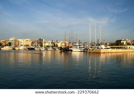 Afternoon.Luxury yachts and sailboats and a small fishing boat in the small Harbor of Zeas,near Piraeus port, Greece - stock photo