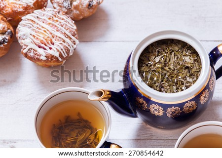 Afternoon tea with cakes on the table top view. Muffins on white vintage grunge table with green tea. The Time of Tea Break.  - stock photo