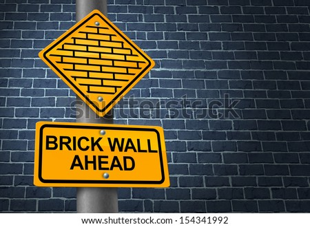 Against A Brick Wall business concept of hardship and difficult restrictions faced on a journey focused on success as a yellow traffic sign warning of a future challenging obstacle obstructing goals. - stock photo