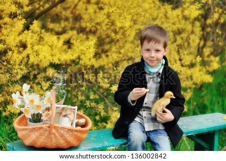 against the background of a flowering bush boy plays in a black coat with a yellow duckling - stock photo