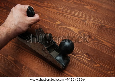 Against the background of a wooden tabletop man holding in his hand planer