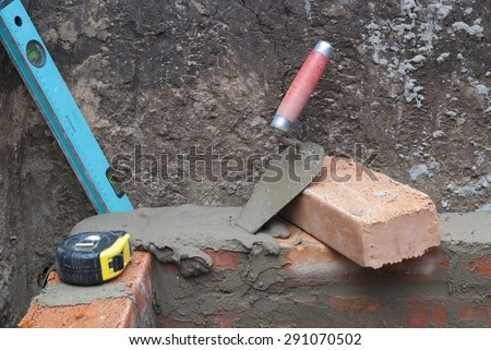 against the background of the brickwork is trowel, level and tape measure - stock photo