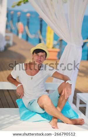 against the sea under a white canopy resting man in a straw hat