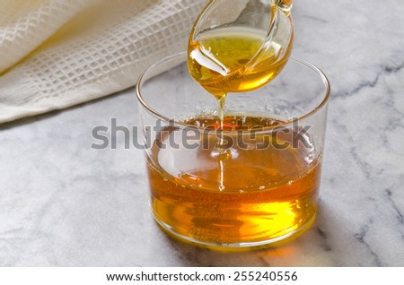 Agave Syrup pouring on a glass. Alternative sweetener to sugar. Selective focus. - stock photo
