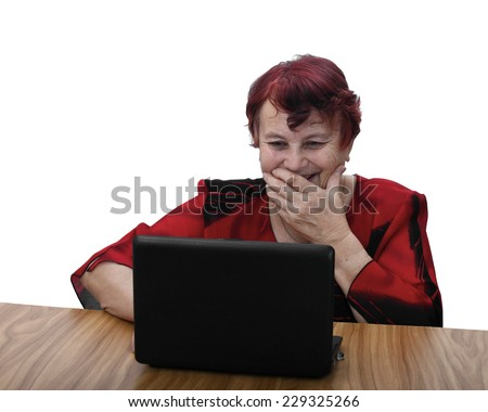 Age is no obstacle to learn modern technologies - senior woman in red dress sits behind table and laughs looking to laptop screen. Portrait isolated on white background - stock photo