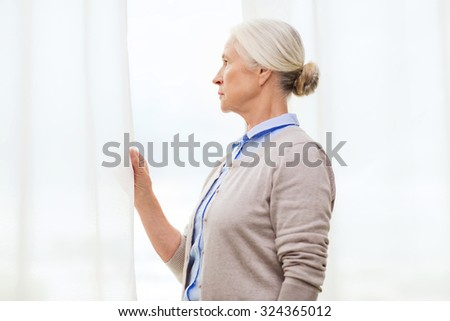 age, loneliness and people concept - lonely senior woman looking through window at home - stock photo