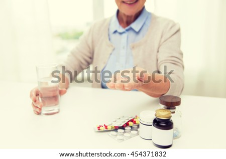 age, medicine, health care and people concept - close up of happy senior woman with pills and glass of water at home - stock photo