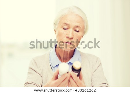 age, medicine, health care and people concept - senior woman looking at jars with medicine at home or hospital office - stock photo