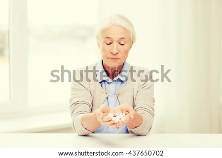 age, medicine, health care and people concept - senior woman with pills at home or hospital office - stock photo