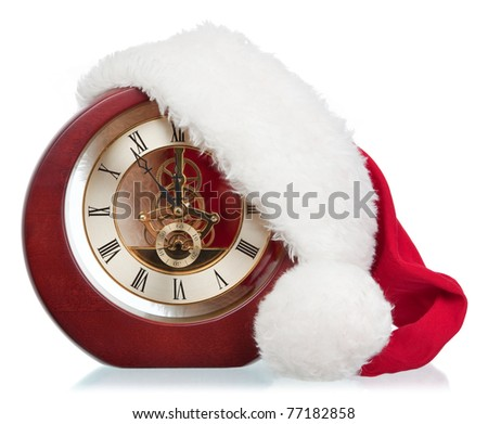 age-old mechanical clock and Christmas hat on a white background - stock photo