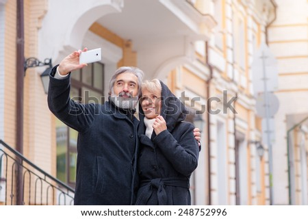 age, tourism, travel, technology and people concept - senior caucasian couple with camera phone taking selfie on street - stock photo