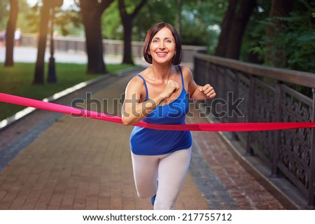 Aged active smiling running woman crosses finish line - stock photo