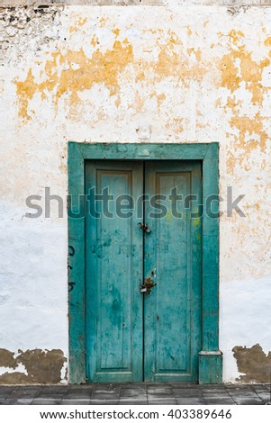 Aged and ancient entrance door on Lanzarote island  Abandoned old building with green painted front door in shabby vintage style, image for travel and architectural blog - stock photo
