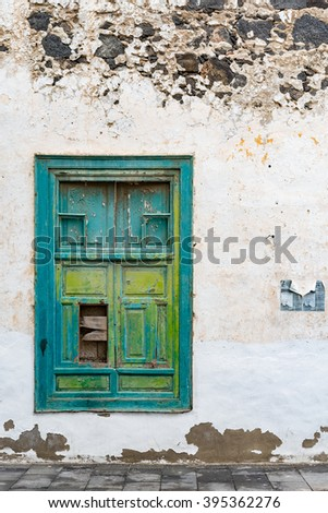 Aged and ancient window on Lanzarote island.  Abandoned old building with green painted shutters in shabby vintage style in Arrecife on Lanzarote, image for travel concept website, architectural blog - stock photo
