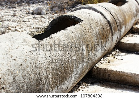 Aged and cracked concrete pipe for watering. - stock photo