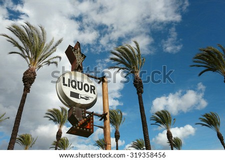 aged and worn vintage liquor sign with palm trees - stock photo