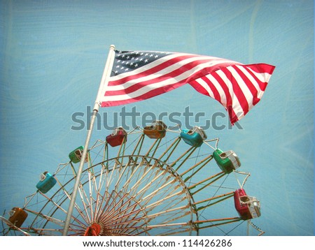 aged and worn vintage photo of american flag and ferris wheel ride - stock photo