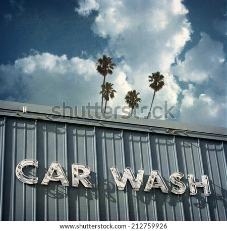 aged and worn vintage photo of car wash with palm tree - stock photo