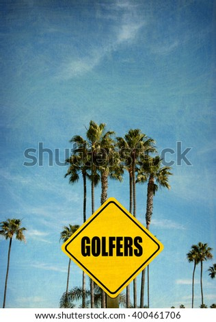 aged and worn vintage photo of caution golfers sign with palm trees - stock photo