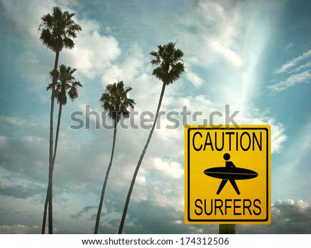 aged and worn vintage photo of caution surfer sign at beach with palm trees                                - stock photo