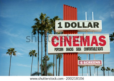 aged and worn vintage photo of cheap dollar cinemas sign with palm trees - stock photo