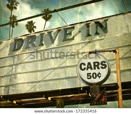 aged and worn vintage photo of drive in movies sign with palm trees - stock photo