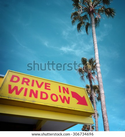 aged and worn vintage photo of drive in window sign and palm trees,  - stock photo