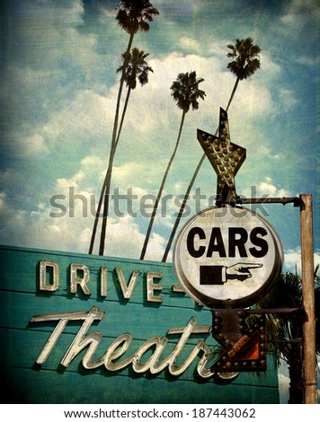 aged and worn vintage photo of drive theater and cars sign with pointing hand                               - stock photo