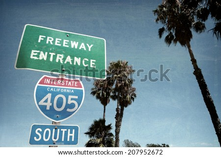 aged and worn vintage photo of freeway sign with palm trees - stock photo