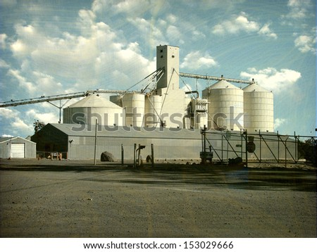 aged and worn vintage photo of industrial agriculture silos                                - stock photo