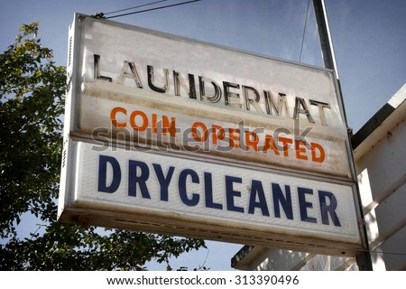 aged and worn vintage photo of laundromat and dry cleaners sign                              - stock photo