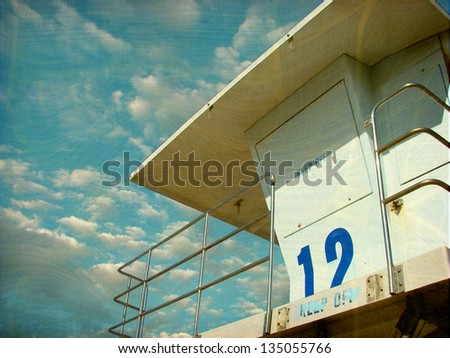 aged and worn vintage photo of lifeguard tower on beach - stock photo