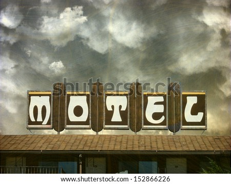 aged and worn vintage photo of motel with stormy sky                                - stock photo