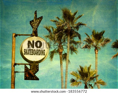 aged and worn vintage photo of no skateboards sign on beach - stock photo