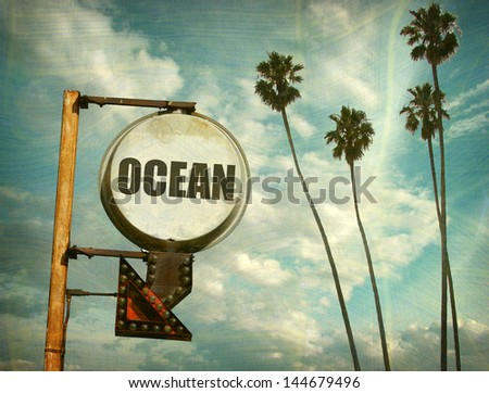 aged and worn vintage photo of ocean sign and palm trees - stock photo