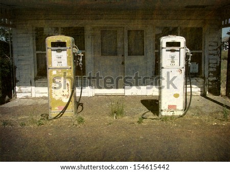 aged and worn vintage photo of old gas station with pumps                                - stock photo