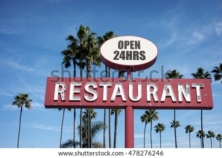aged and worn vintage photo of old neon restaurant sign with palm trees