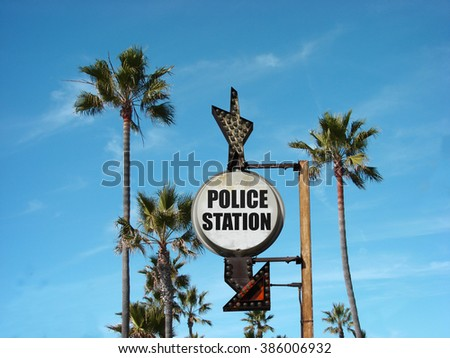 aged and worn vintage photo of police station sign with palm trees