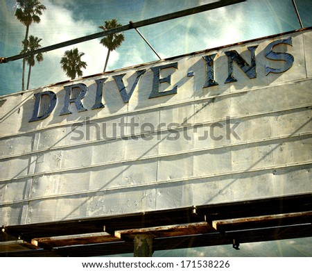 aged and worn vintage photo of retro drive in sign with palm trees - stock photo